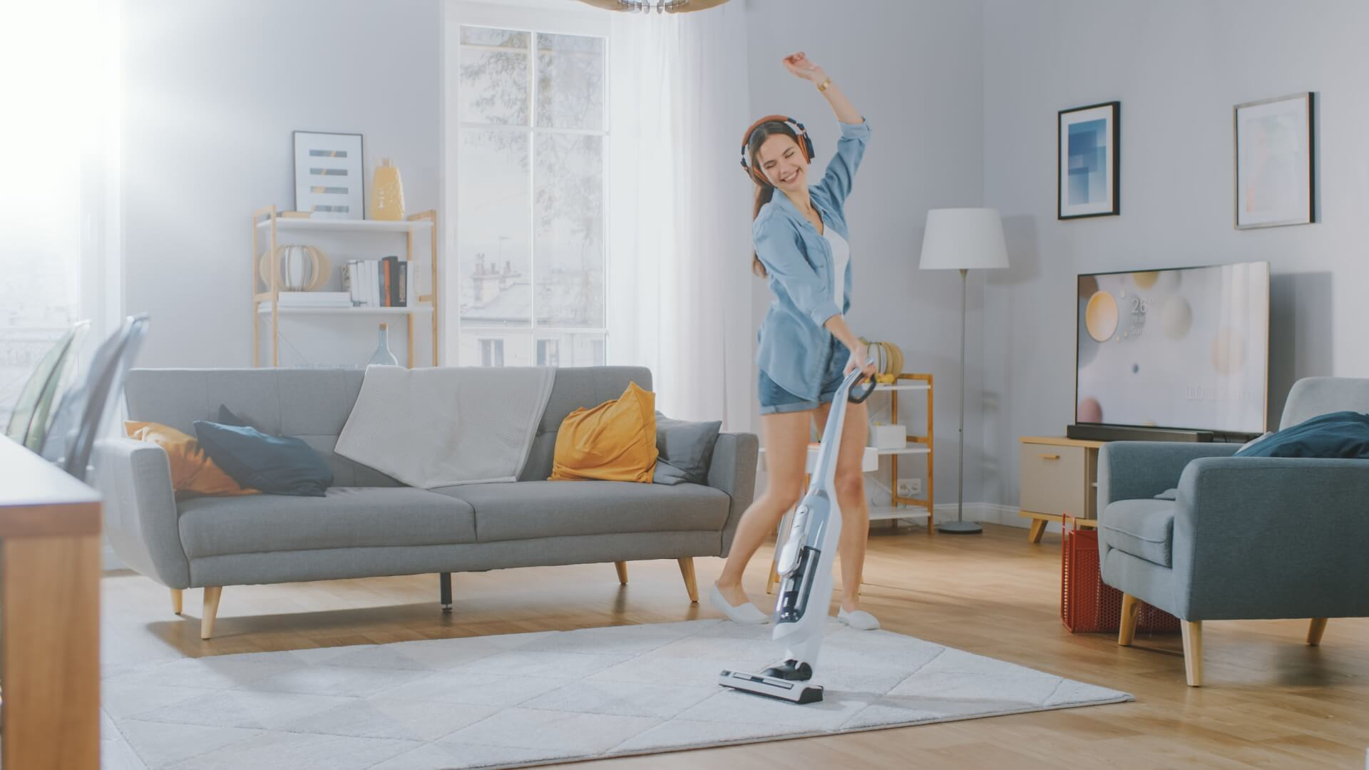 A Beautiful Woman is Cleaning a Carpet in a Cozy Room. She Uses a professional Vacuum.