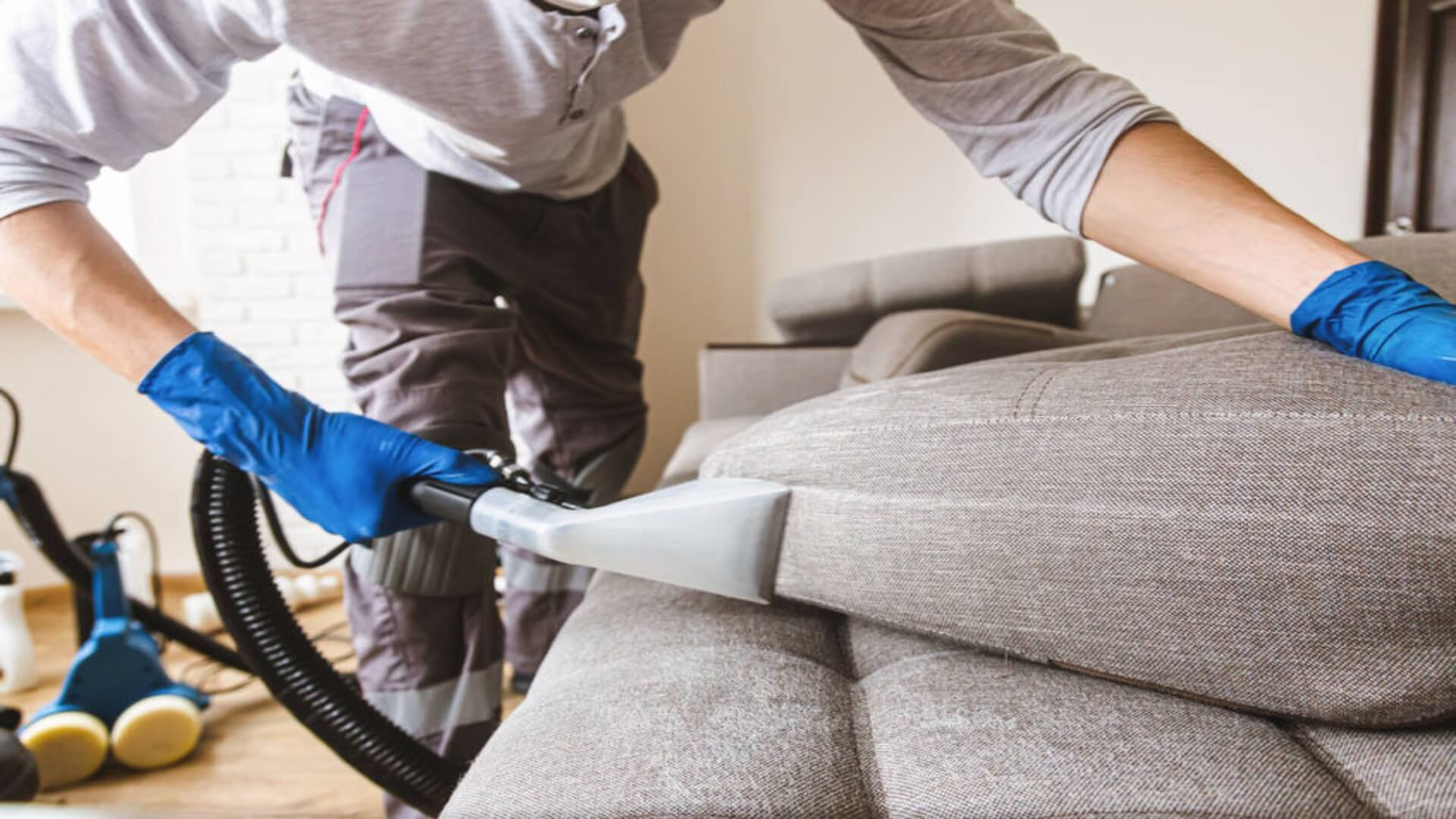 Professional cleaning of the sofa upholstery. The man is cleaning the upholstery with a vacuum cleaner. pholstery cleaner to hire.