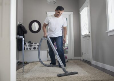 A man cleans the carpet with a professional vacuum cleaner. Deep carpet cleaning in a cozy room.