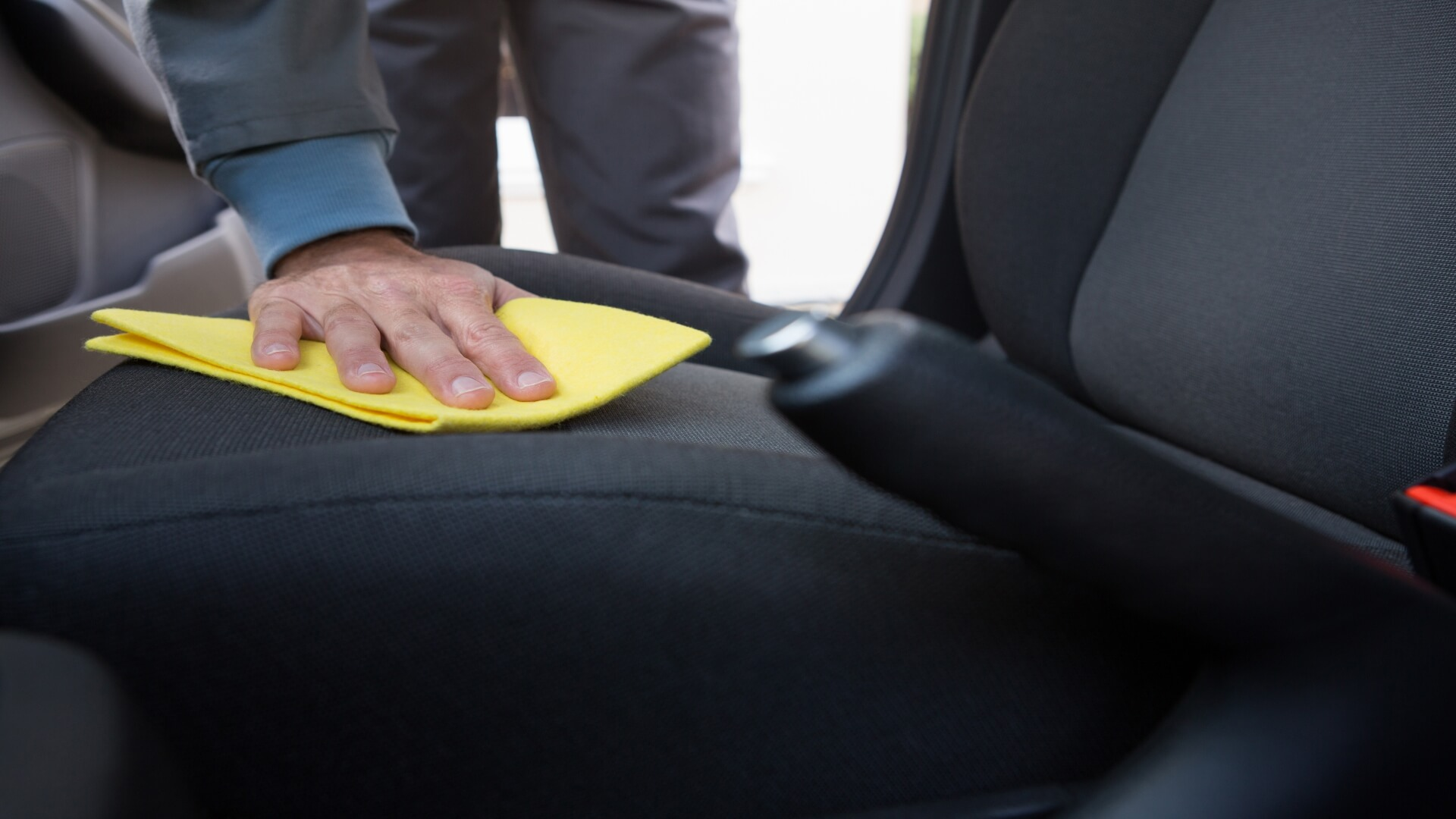 Car upholstery cleaned by a man. Cleaning car seats, cleaning vehicle upholstery.